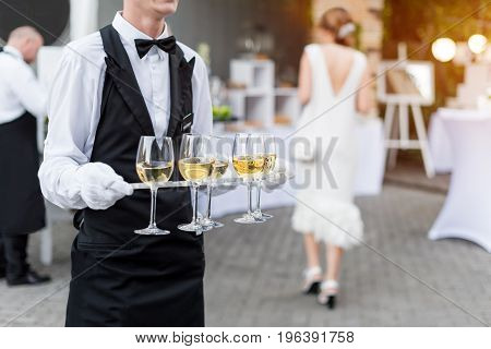Midsection of professional waiter in uniform serving wine during buffet catering party, festive event or wedding. Full glasses on tray