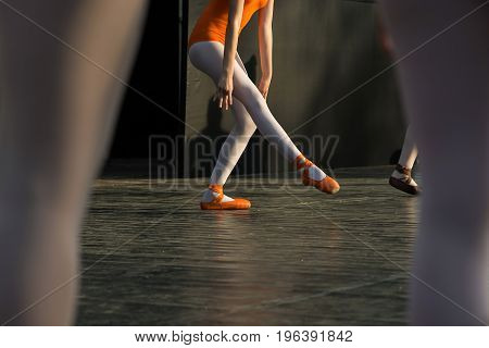 Ballerina feet dancing on ballet shoes on stage during a performance.