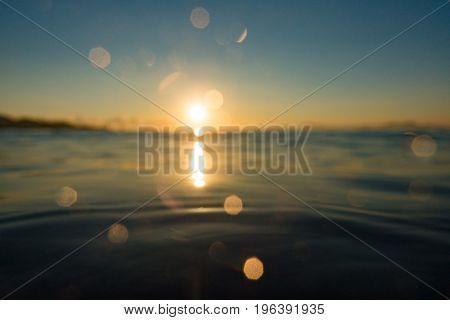 Sunset with underwater part  by waterline. Blurred background