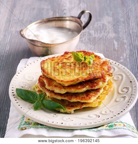 Stack of zucchini and feta fritters on plate square image