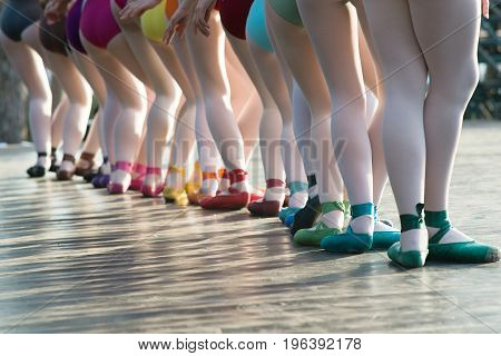 Ballerinas feet dancing on ballet shoes with several colors on stage during a performance.