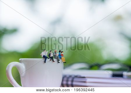 Miniature businessmans readinging book and sitting on the cup of coffee with glasses and notebook background using as a business concept.