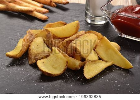 Rustic fried potatoes with shell on stone dish,ketchup sauce and salt.