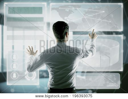 Back view of young businessman pointing at/ pressing buttons of digital business projection. Technology innovation and analytics concept. Double exposure