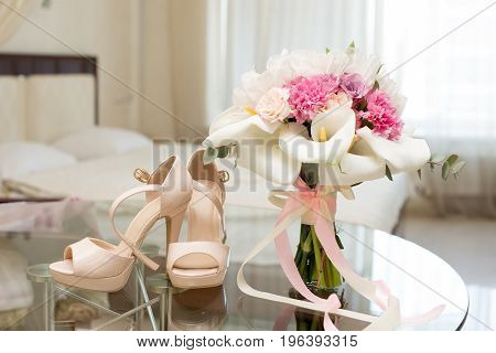 Luxury the bride's shoes and With wedding bouquet of the bride on the table.