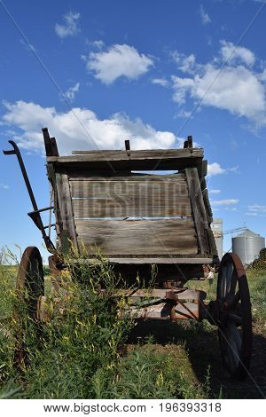 The back of an old rickety wood wagon for hauling supplies and grain with a side brake