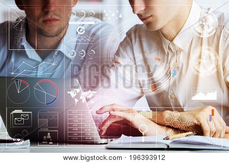 Close up of businessmen using laptop placed on office desktop with objects and abstract business hologram. Technology future and teamwork concept. Double epxosure