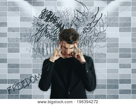 Pensive young businessman on tile background with scribble. Confusion concept