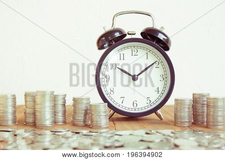 Stack of coins with black fashioned alarm clock for display planning money financial and business accounting concept time is money concept with clock and coins time to work at make money vintage color tone