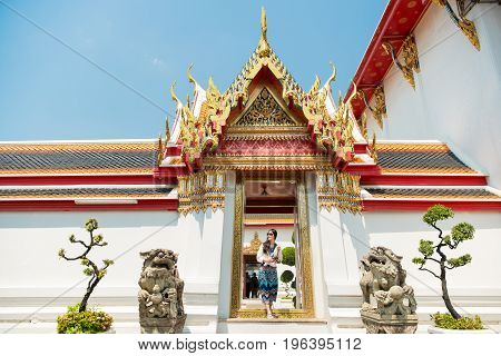 Thailand travel at Wat Pho temple. Tourist in Asia walking on famous Thai tourist destination and attraction in Bangkok. Woman traveler walking in temple enjoying her summer vacation.