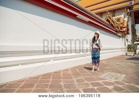 Bangkok travel tourist woman on vacation in Wat Pho walking . Person in dress visiting the famous temple with walking on sidewalk of old white temple wall. Asia summer destination.