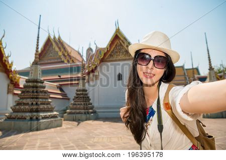 Asian japanese woman taking self portrait selfie photo with smartphone camera on asia travel. Happy candid tourist on wat pho temple building the old town of Bangkok Thailand.