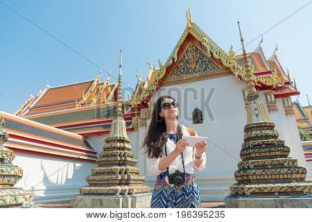 young elegant female backpacker using mobile digital tablet computer reading guidebook app searching information on Bangkok wat pho temple in Thailand travel.