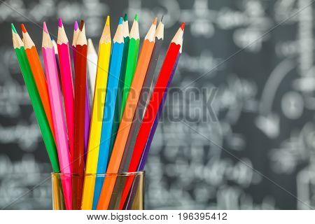 Back to school background with colorful pencils and the title