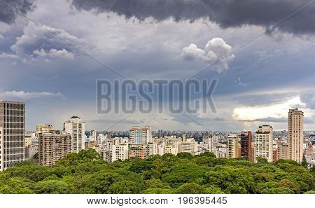 View of buildings skyline and Parthenon park in Sao Paulo from Avenida Paulista on a day with lots of clouds