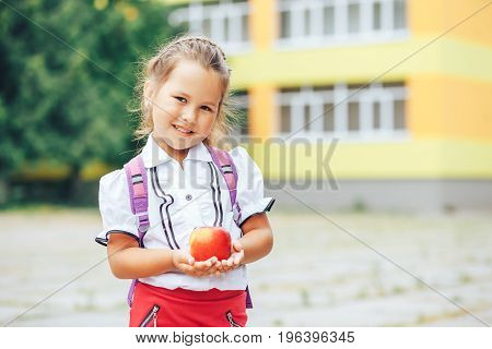 Girl goes to school and holds a red apple in her hand