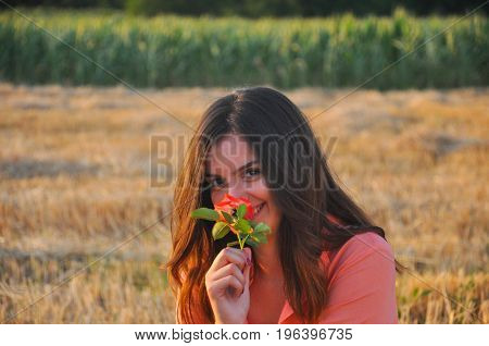 Beautiful girl smells rose. Portrait of young woman smell roses in nature