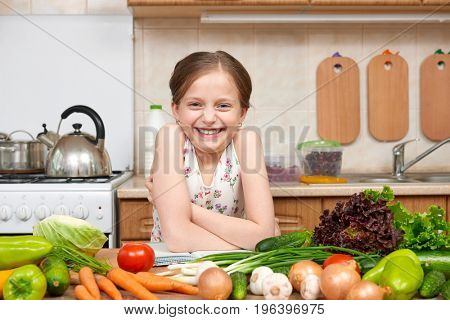 child girl with fruits and vegetables in home kitchen interior, read cooking book, healthy food concept
