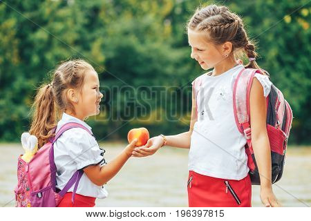 The older sister shares her apple. Two girls in the background of the school.