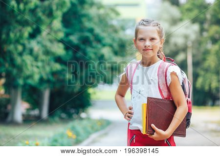 Smiling little girl goes to school with a book and holds book in her hand