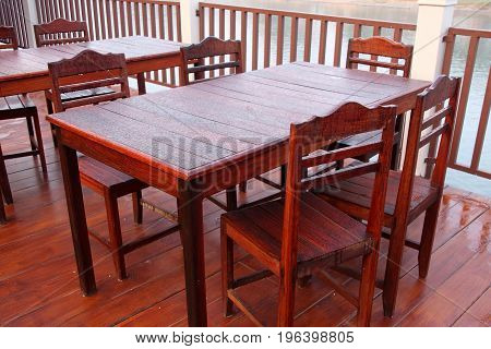 Wooden table and chairs covered in dew drops