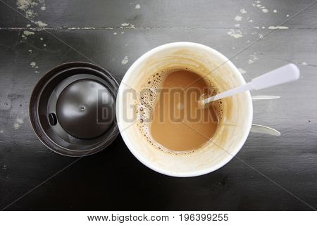 Hot coffee in paper cup on black seen from top.