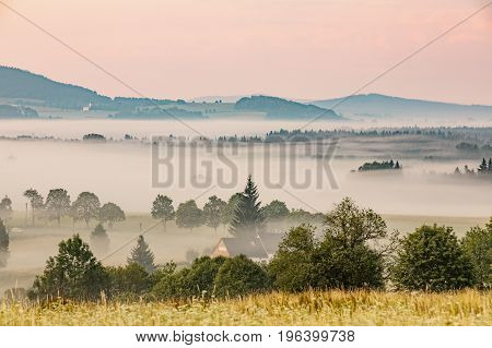 Summer landscape in fog Sumava Czech Republic. Morning fog in Sumava south Bohemia landscape