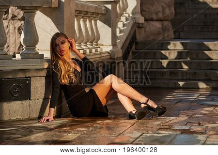Beautiful blonde lady in black dress with decolletage at Park and Horses fountain in Alexander Garden at the Maneschnaja road Moscow Russia