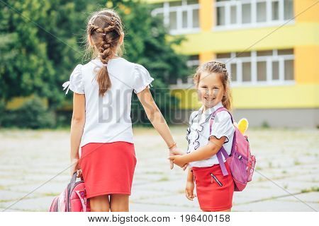 The older sister takes the younger from school. Two schoolgirls go for hands