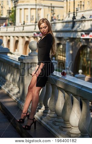 Beautiful blonde lady in black dress with decolletage posing near baluster railing