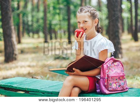 Smiling sweet girl after school eating red apple and teaching lessons