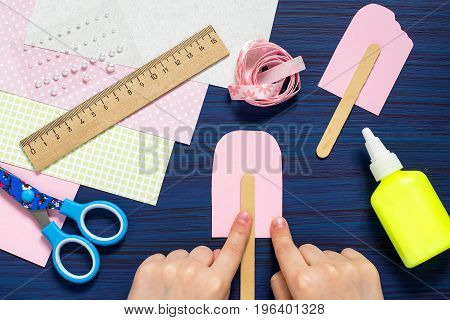 Child makes card with ice cream. Summer theme. Original children's art project. DIY concept. Step-by-step photo instruction. Step 5. Child glues ice cream sticks