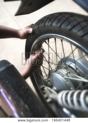 Men's hand is filling the motorcycle tire.