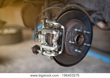 car wheel brake disc and shoes of lifted automobile at repair service station