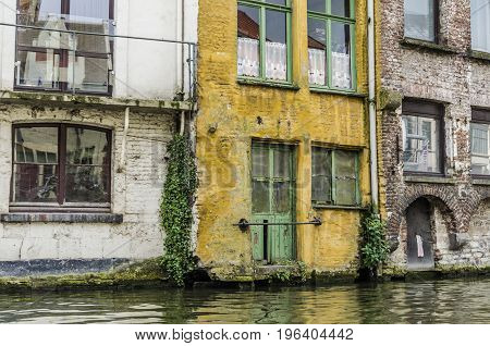 Old and colorful houses on the edge of a canal of Belgian gent