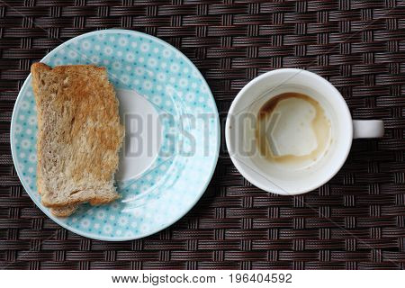 Empty coffee cup and half toast on dish.