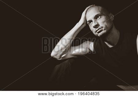 Depression. Depressed miserable young man sitting alone in the dark with emptiness in his eyes. Dark image. Dark background. With film grain.