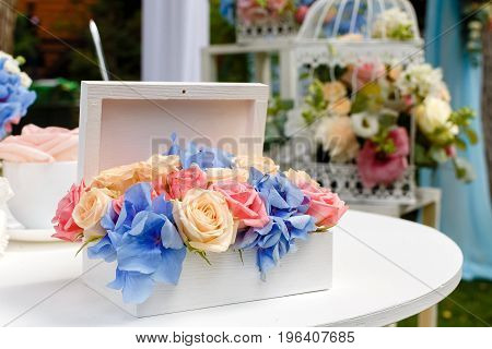 Wedding ceremony decorations bouquets of roses at the table in restaurant outdoors.