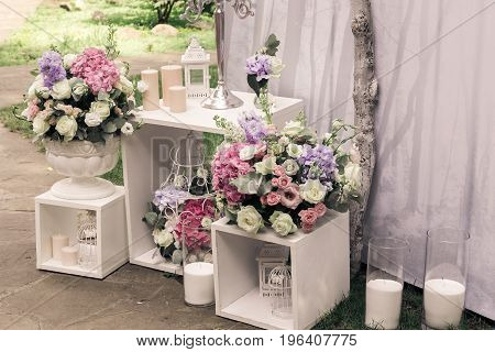 Wedding ceremony decorations bouquets of flowers roses and eustoma candles in restaurant outdoors.