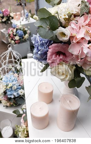 Wedding ceremony decorations bouquets of roses and eustoma candles in restaurant outdoors.