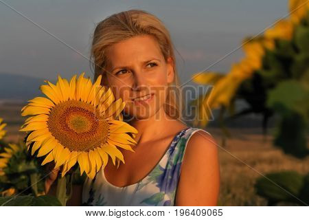 Beautiful blond woman enjoys sunset and blooming sunflowers. Relaxation. Nirvana.