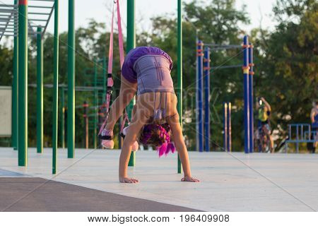workout with suspension straps In the outdoor gym, fit woman training early in morning on the park, sunrise background