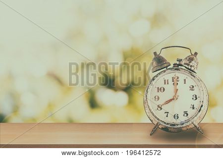 Vintage of retro alarm clock on wooden table nature and green bokeh background