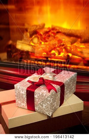 Christmas gift boxes with red ribbon in the interior with a fireplace