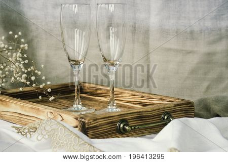 Pair of wine glasses and wooden tray champagne flutes on the wedding table Mockup. Vintage rustic style.