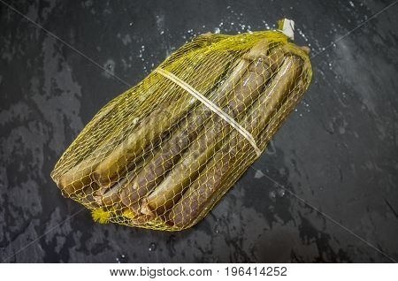 Bundle of razor clams in their plastic net isolated over black slate