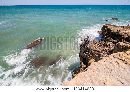 Brave Man Enjoy Watches The Ocean On Top Of The End Of The Cliff, Rock In Beautiful Rock Beach. Summ