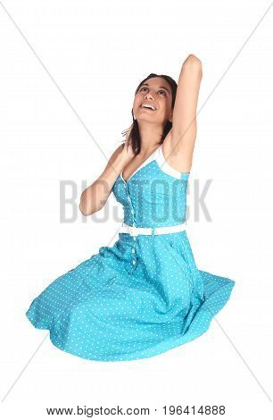 A beautiful Hispanic young woman sitting in a blue dress on the floor laughing with her mouth open isolated for white background.