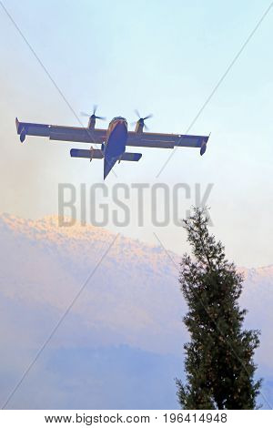 Zrnovnica Split Croatia - July 17 2017: Canadair airplane gas the massive wildfire burning down the forest and villages around city Split