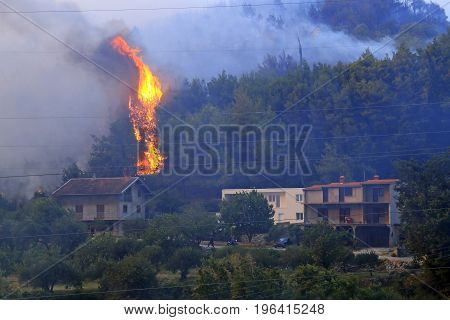 Zrnovnica Split Croatia - July 17 2017: Flames jumping over the house during massive wildfire burning down the forest and villages around city Split